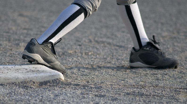 スパイクでベースを踏む野球選手